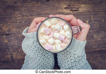 Cozy winter home background. Glass of hot cocoa with mini...