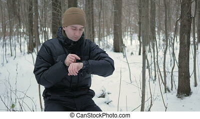 A man checks the messages on the smart watch in the winter...