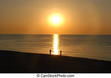 Couple enjoying amazing sunrise on the beach