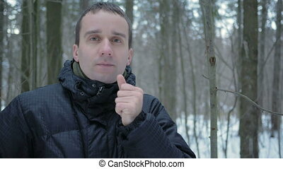 A young man in winter forest freeze. He's breathing on his hands, rubs and wears a hat and gloves. Snowy landscape. He looks into the camera