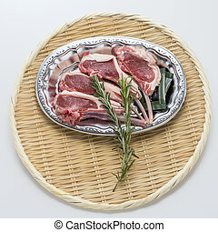 Fresh red beef cow ribs with rosemarry on bamboo tray