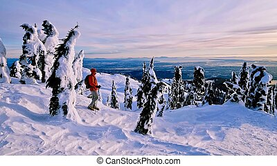 Man snowshoeing in mountains with beautiful view.