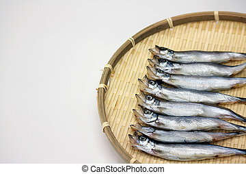 Dried Capelin fish on bamboo tray in white background in...