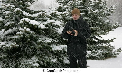 A young man in winter is cold in the forest near the spruce. Big snowfall. He's breathing on his hands, rubs and wears gloves with a hood. Snowy landscape. He looks into the camera