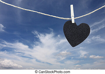 Black Heart hung on hemp rope on blue sky background. -...