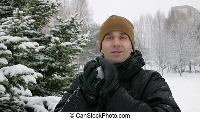 A young man looking at the camera and playing with snow in winter forest. It makes snowballs and throwing them. Winter fun concept