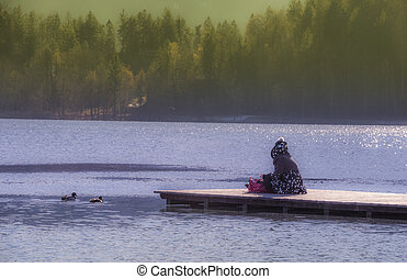 Young woman sitting on lake Bleds pier