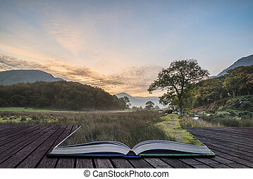 Beautiful foggy misty Autumn sunrise over countryside surrounding Crummock Water in Lake District in England coming out of pages of book