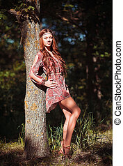 Portrait of beautiful young hippie girl standing near the...