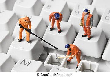 Worker figurines computer keyboard - Worker figurines posed...
