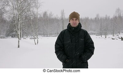 The young man looks into the camera and smiling in winter...