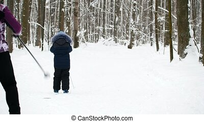 Sport childhood - boy skier walking in winter snow forest,...