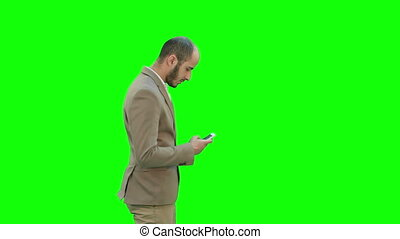 Business man walks in texting on the phone on a Green Screen, Chroma Key.