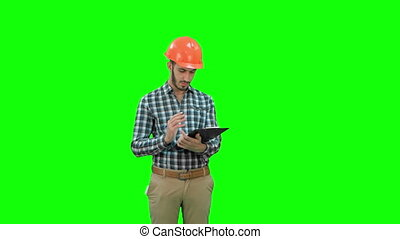 Civil engineer filing in inspection form on a Green Screen, Chroma Key.