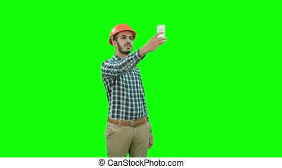 Construction worker using phone to take selfies on a Green Screen, Chroma Key.