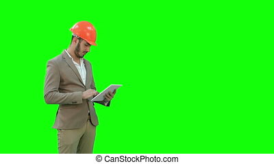 Engineer in safety helmet conducting inspection with tablet...