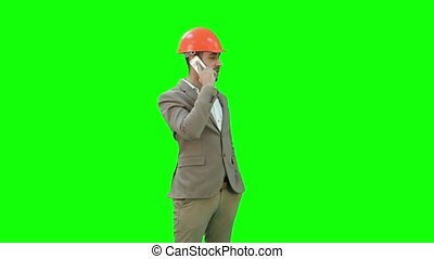 Contractor in hardhat talking on his cell phone on a Green Screen, Chroma Key.