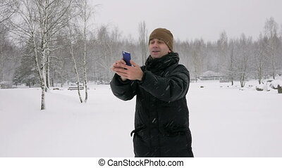 Man makes selfie phone in a snowy winter forest. He smiles...
