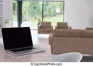 Notebook with blank screen on table in luxury living room.
