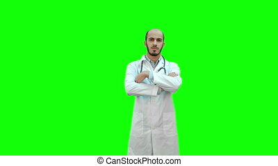 Serious medical worker standing with his arms across his chest on a Green Screen, Chroma Key.