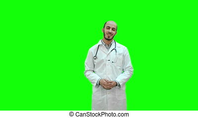Smiling doctor talking to the camera on a Green Screen,...