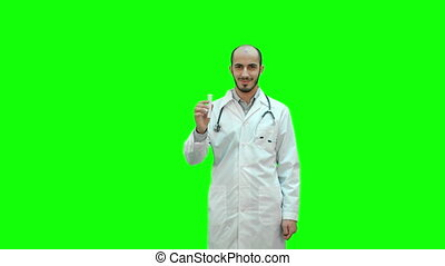 Smiling doctor in uniform pointing at medicine bottle and looking at camera on a Green Screen, Chroma Key.