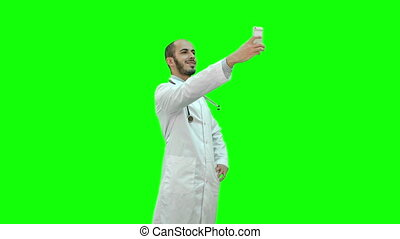 Smiling doctor in white coat with stethoscope taking selfie on his phone on a Green Screen, Chroma Key.