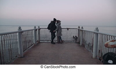 couple man and woman on the pier watching the sea and...