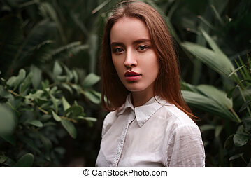 Young woman standing at a greenhouse with exotic plants and...