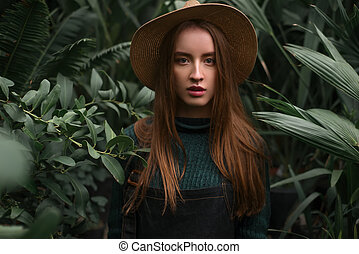 Woman standing at nursery in a greenhouse - Young baeutiful...