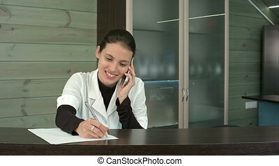 Smiling spa receptionist talking to client over the phone...