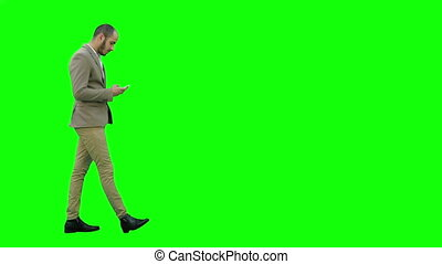 Business man walks in checking up his phone on a Green Screen, Chroma Key.