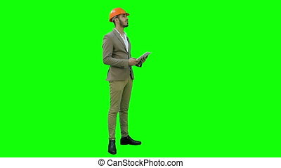 Engineer in helmet carrying out inspection using tablet on a Green Screen, Chroma Key.
