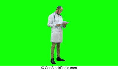 Male doctor checking medical documents on a Green Screen,...