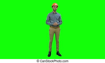 Happy young engineer wearing helmet talking to the camera on a Green Screen, Chroma Key.