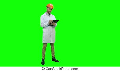 Civil engineer in white coat preparing report on a Green Screen, Chroma Key.