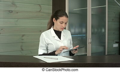 Smiling spa receptionist putting her tablet aside to greet...
