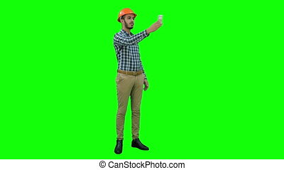 Smiling construction worker using phone to take selfies on a Green Screen, Chroma Key.