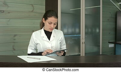 Woman at spa reception desk uses tablet pc texting to...