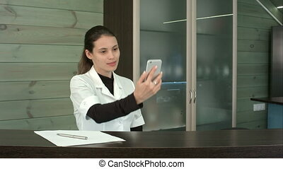 Happy beauty salon receptionist taking funny selfies with...
