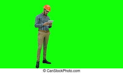 Engineer using a wireless tablet to check construction project on a Green Screen, Chroma Key.