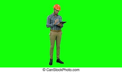 Site inspector filing in inspection form on a Green Screen,...