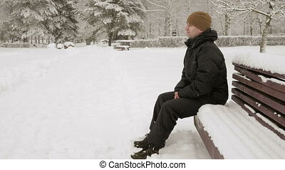 A young man sits on a bench in winter park and admiring the...