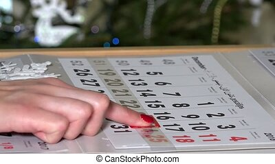 finger push paper calendar marker on December last days in...