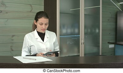 Beauty salon receptionist uses tablet pc to write down...