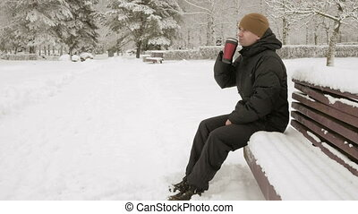 A young man drinking a hot beverage from a thermos in a...
