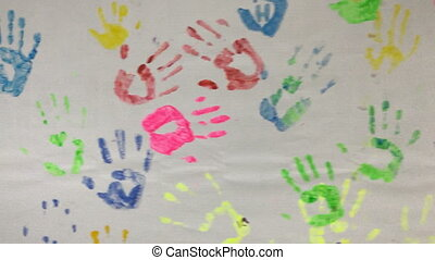 Multi-colored prints of hands of people on the wall close-up