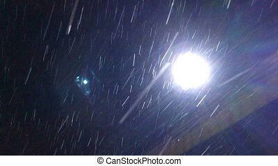 Snow falls on the background of a bright source of light at...