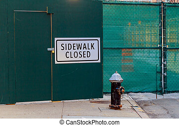 SIDEWALK CLOSED sign posted on green construction wall...