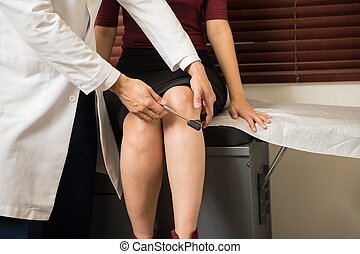Doctor checking a woman's reflexes - Closeup of a male...